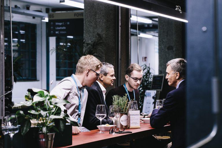 Vier Männer stehen an einem Tisch und unterhalten sich